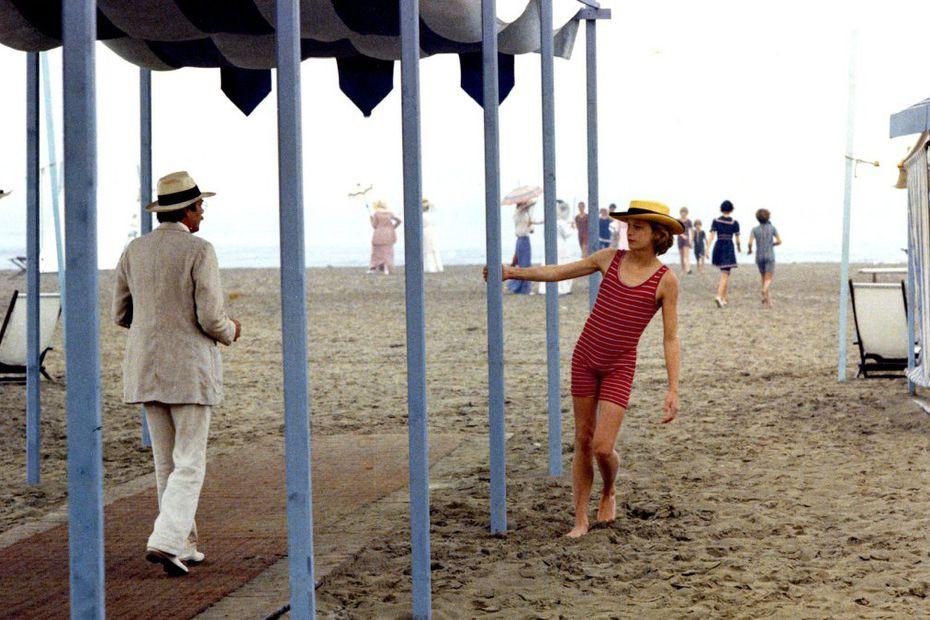 Photo du film La Mort à Venise, Luchino Visconti, Dirk Bogarde, Björn Andrésen, un homme en costume blanc croise un adolescent en tenue de bain sur une plage du Lido à Venise