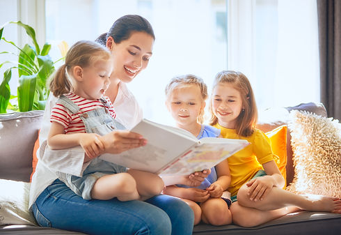 mom-and-children-reading-a-book-SUEGTLK.