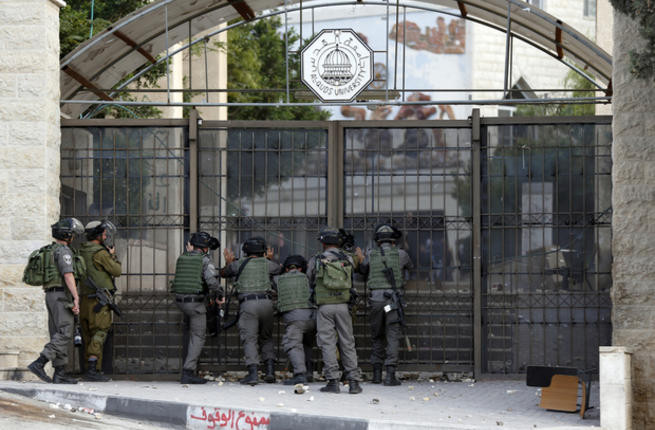 Israeli guards stand outside the gate of al-Quds University in 2015. (AFP)