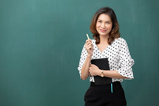 asian teacher holding chalk and book on