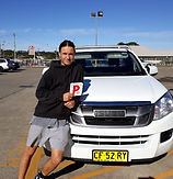 Rhys standind next to his car with P plates showing