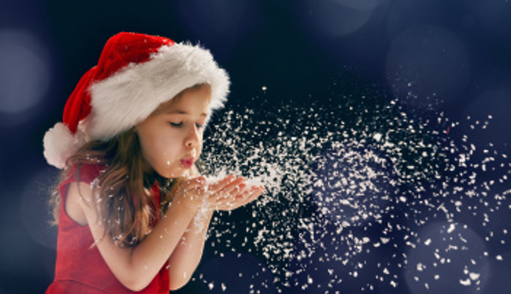 girl blowing on snow