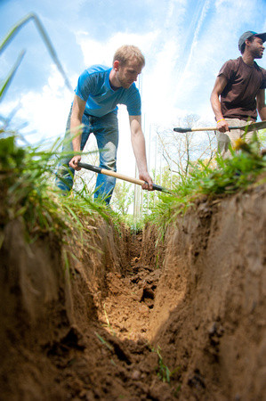 Man with shovel digging trench