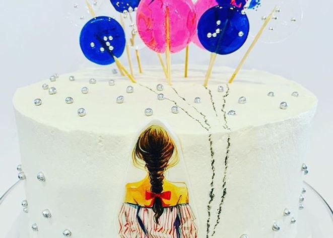 Girl holding balloons cake.jpg