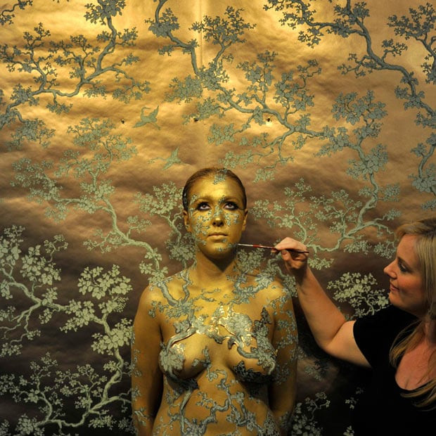A model is painted by artist Emma Hack in London. Hack, a leading skin illustrator, is painting naked models at the Art London fair, camouflaging them against a wallpaper background designed by Australian interior designer, Florence Broadhurst.
