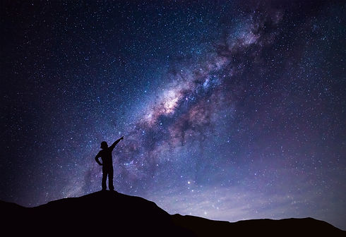 Milky Way landscape. Silhouette of Happy woman pointing to the bright star._edited.jpg