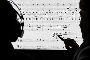 Two people working on a musical score using computer notation software. Not a real score, notes rand