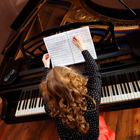 Young woman musician writes in music book pencil..jpg