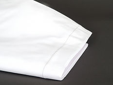 White folded Marie l'Oie bedsheet which slips right onto your mattress.