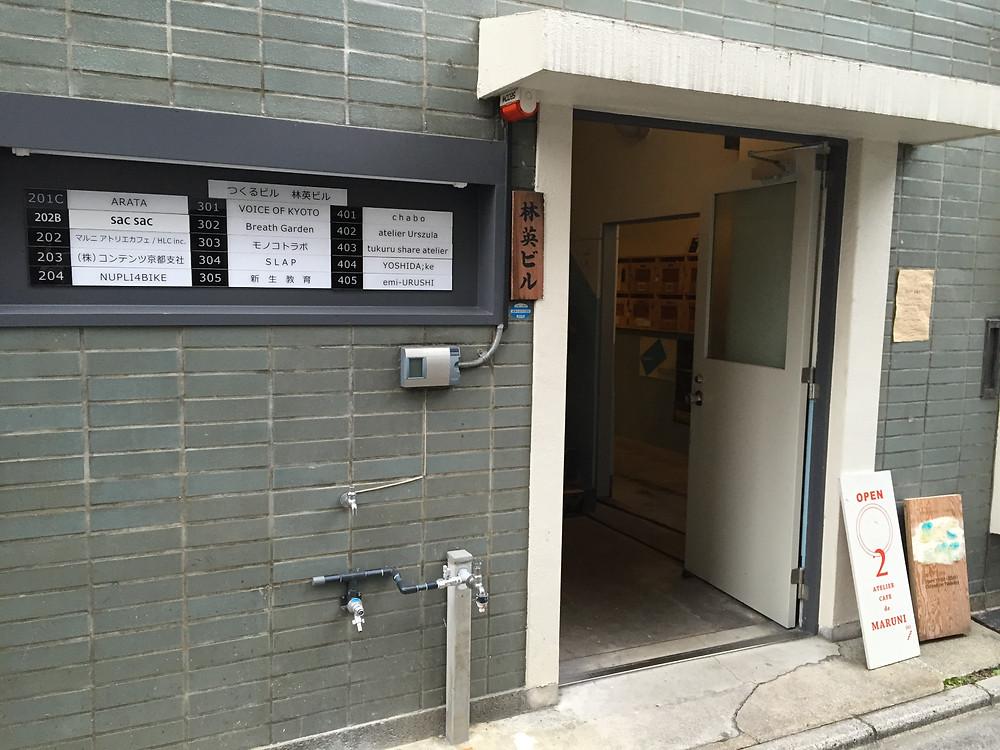つくるビルに入っているテナントさんの看板があり、入り口すぐに階段を上がるとマルニアトリエカフェさんです。