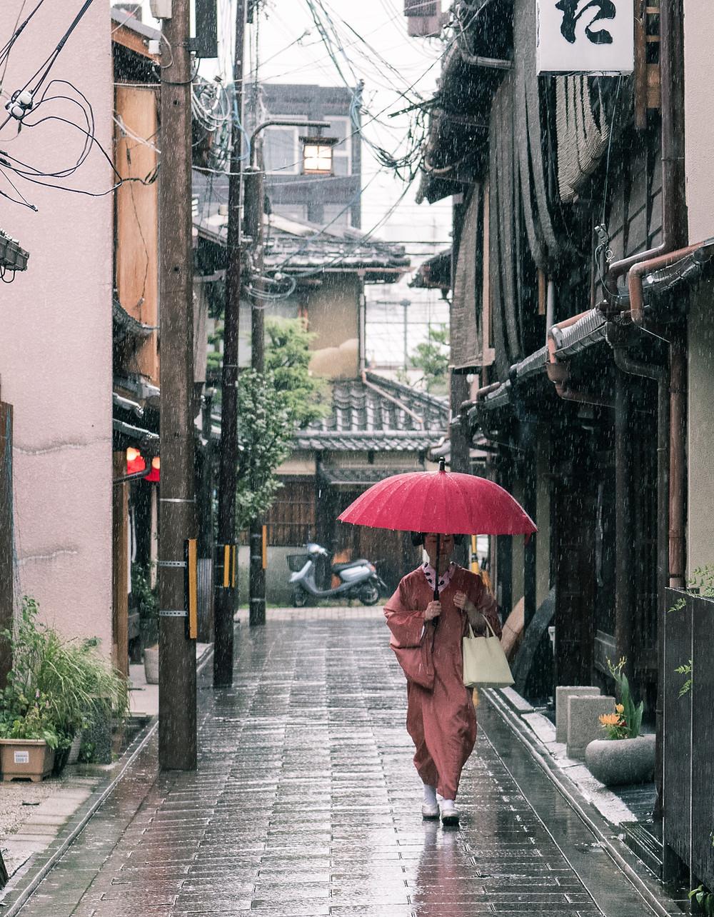 Geisha con l'ombrello sotto la pioggia di Kyoto