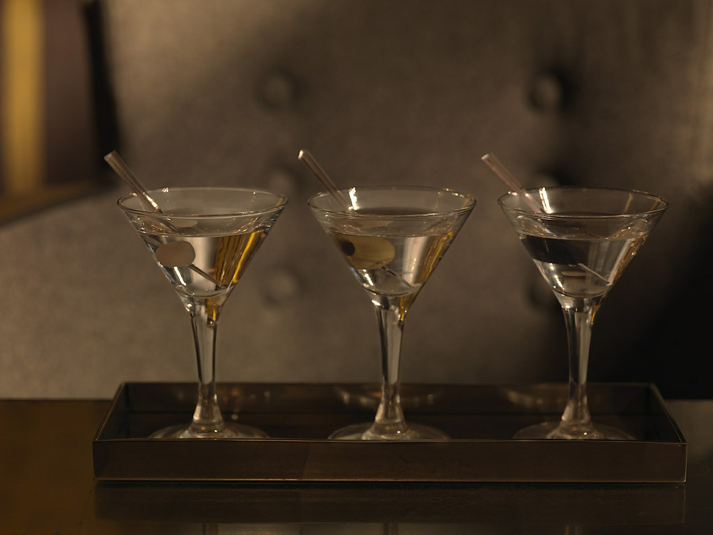 Three martini glasses with olive garnish