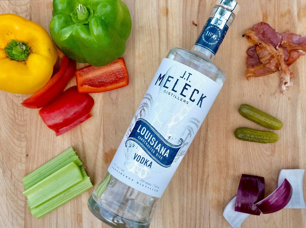Ultimate Bloody Mary ingredients: bell pepper, celery, purple onion, pickles, bacon, and a bottle of JT Meleck Vodka