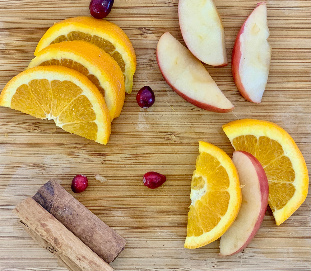 Orange slices, apple slices, and cinnamon sticks.