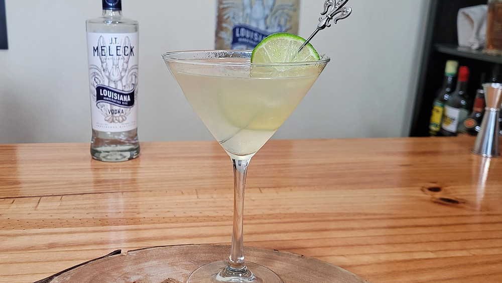 Cocktail in a martini glass with a lime.