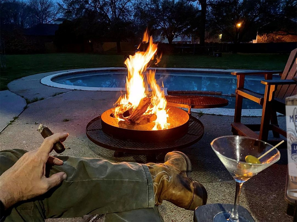 Man in boots holding a cigar in front of a fire