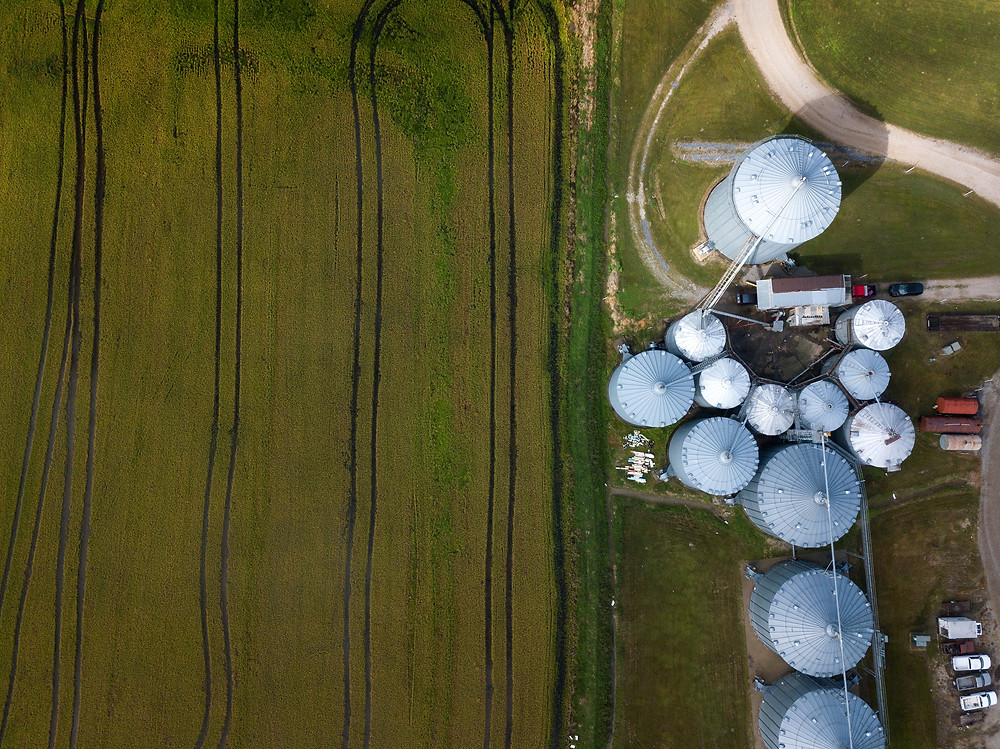 Aerial view of flooded rice fields and silos.