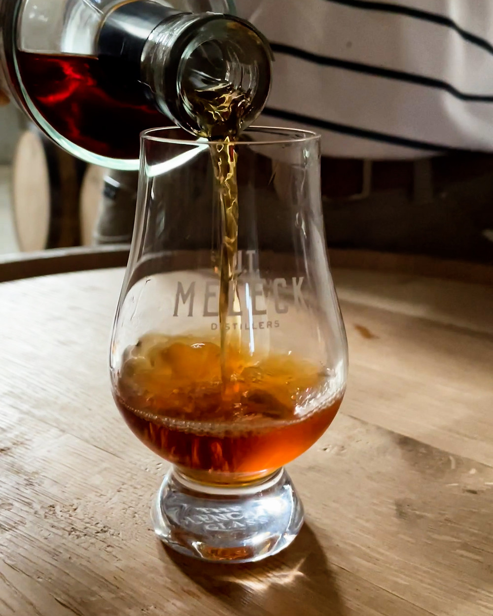 Whiskey being poured into a whiskey glass.