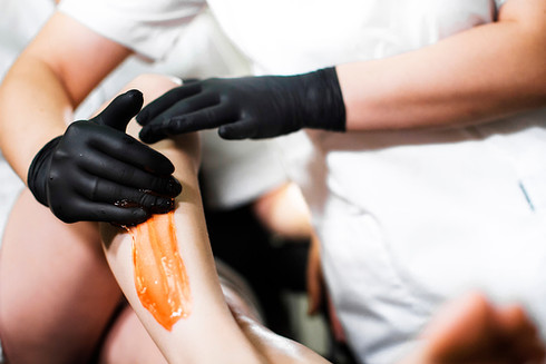 Beautician in black latex gloves apply s