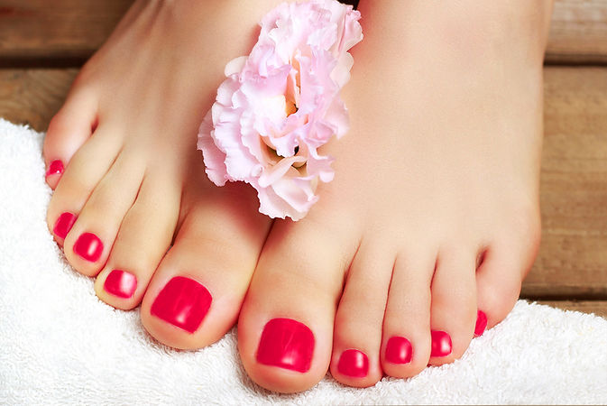 Pink pedicure with flower close up on wo