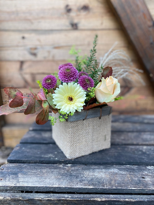 Seasonal flowers in hessian pot