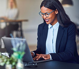 Smiling young African American businesswoman working on a laptop at her desk in a bright m