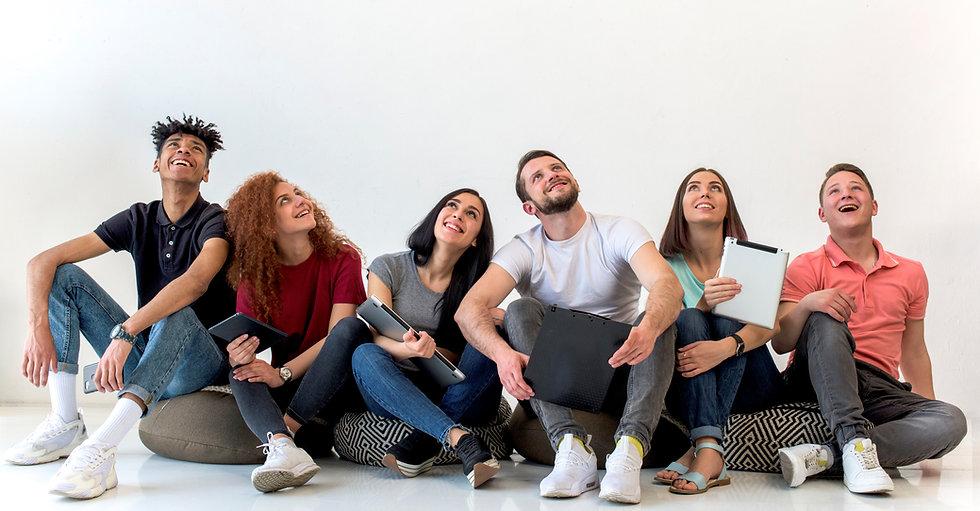 multiethnic-friends-sitting-floor-lookin