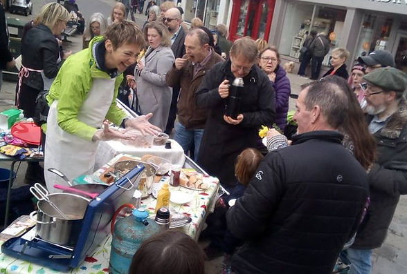 Two volunteers at a stall surrounded by people eating vegan food and talking.