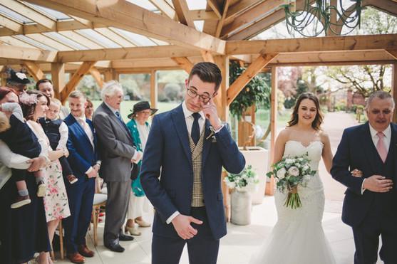 Candid emotional crying groom as bride walks down aisle at Gaynes Park Essex