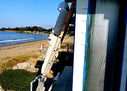 A house painter working on the exterior of a house in Summerland CA