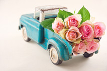 Old antique toy truck carrying pink rose