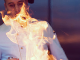 Chef cooking and doing flambe on food in