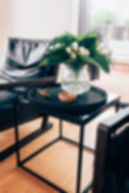 Interior side table setting with vase and ornaments next to leather chair