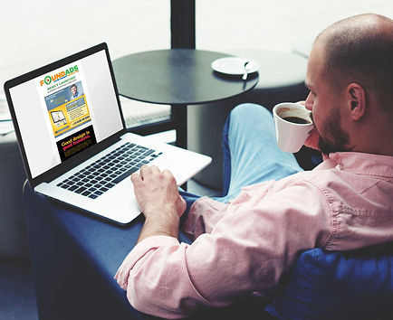 Man scrolling Found Ads website on laptop with coffee