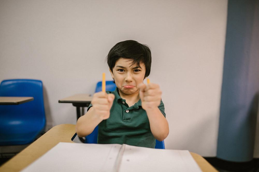 An unhappy boy at his school desk snaps his pencil