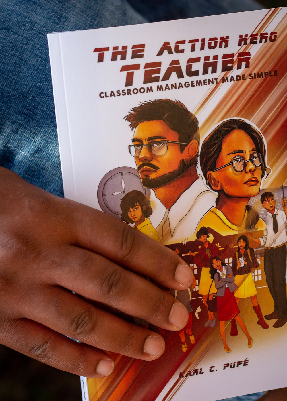 "A close-up of a hand holding ""The Action Hero Teacher"" book"""