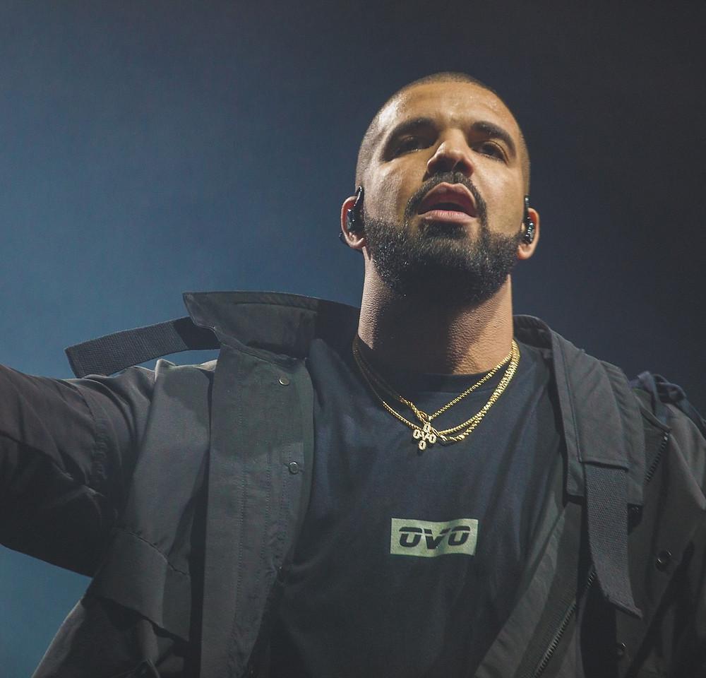 Rapper Drake wearing a black military jacket & black OVO shirt