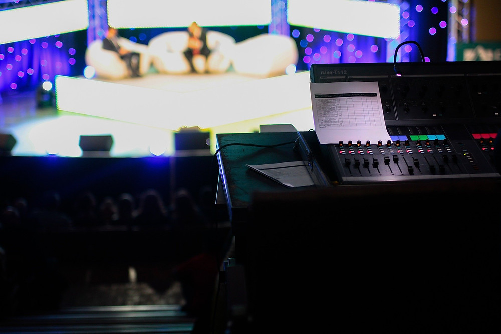 A close up of a mixing desk overlooking a TV studio