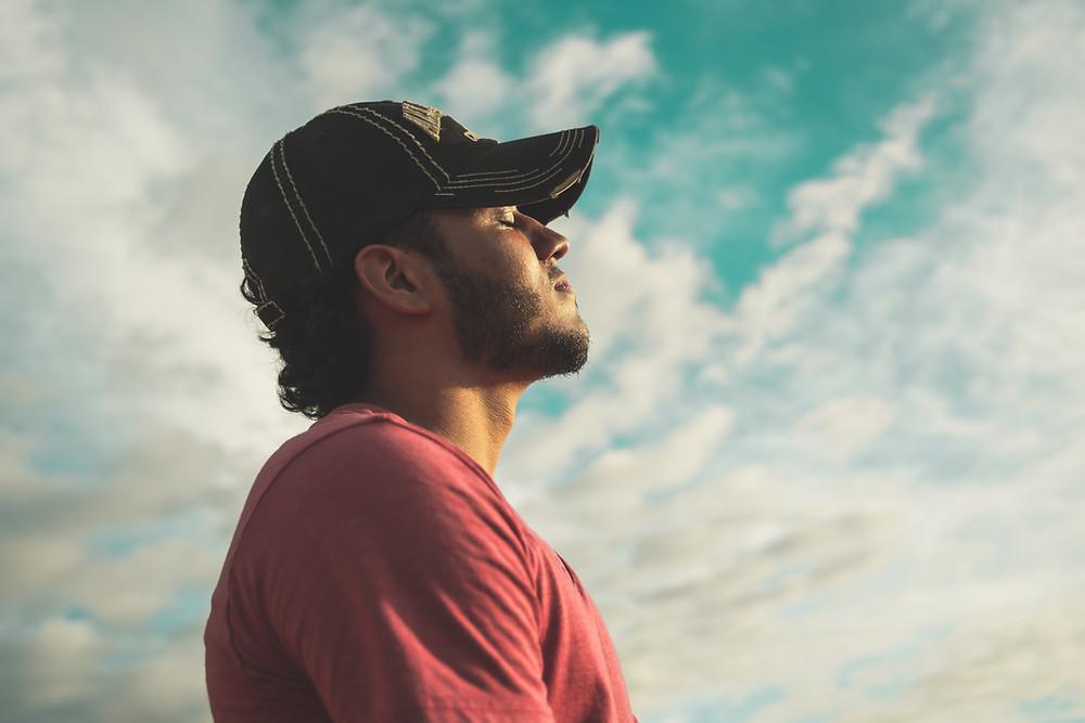 A man in a cap closing his eyes in meditation