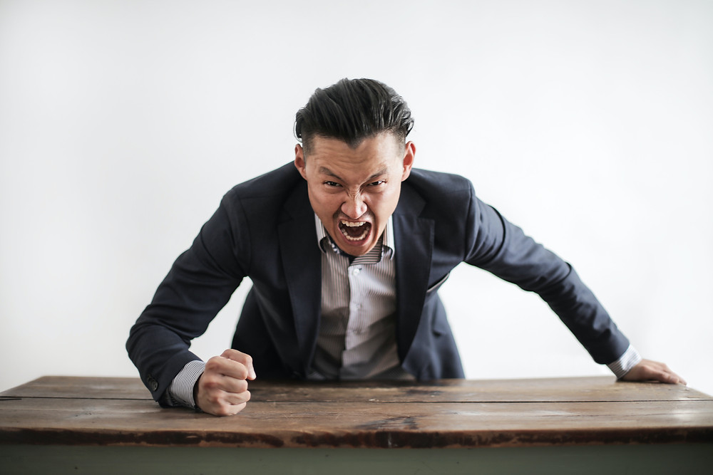 A man screaming & pounding a desk with his fist