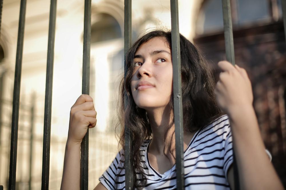 A girl holding unto a fence.