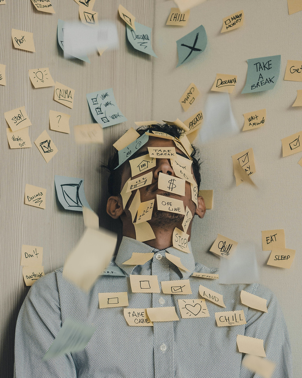 A man lying down covered in post-It notes