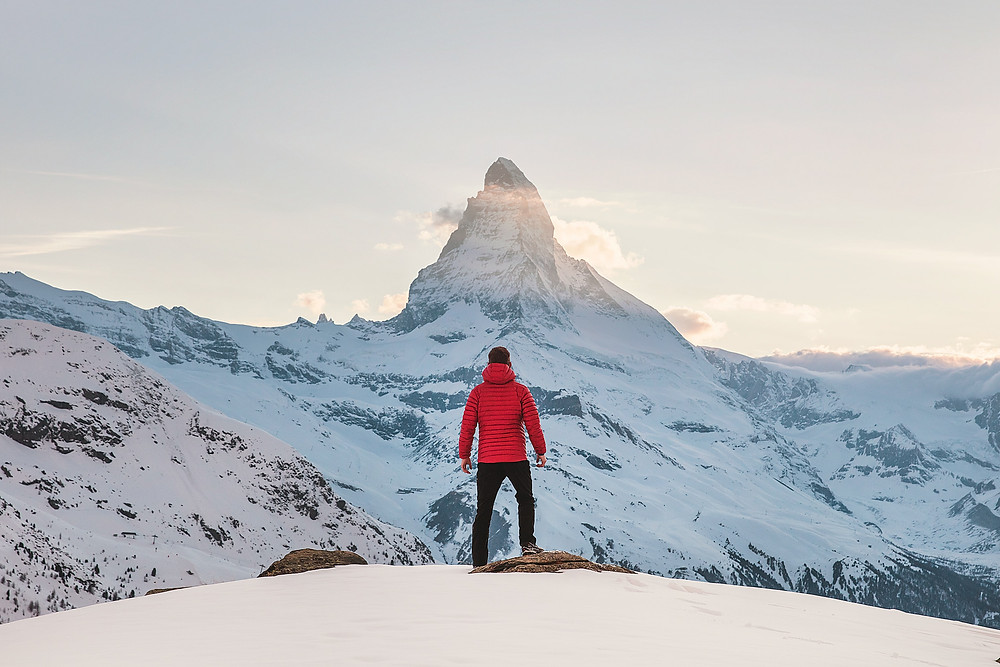 A man on a snowy hill staring at a mountain