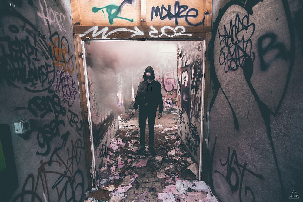 A hooded man standing in a messy graffitied room