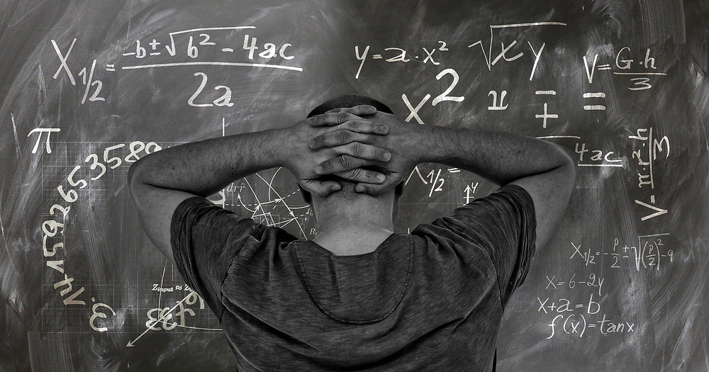 The back of a man with his hands behind his head starting at a blackboard of maths formulas