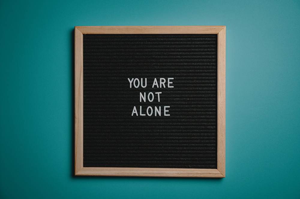 A blackboard saying 'You Are Not Alone'