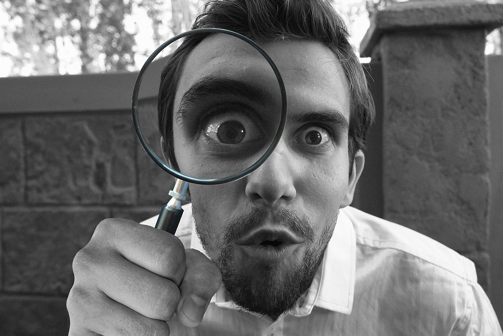 A close-up of a man looking at the camera with a magnifying glass