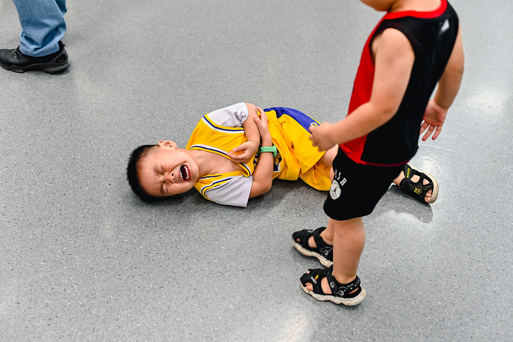 A boy on the ground screaming while another one stands over him