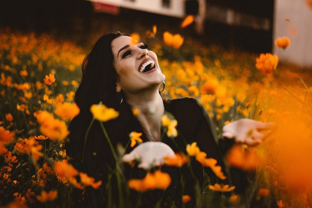joyful woman sitting in a field of orange flowers