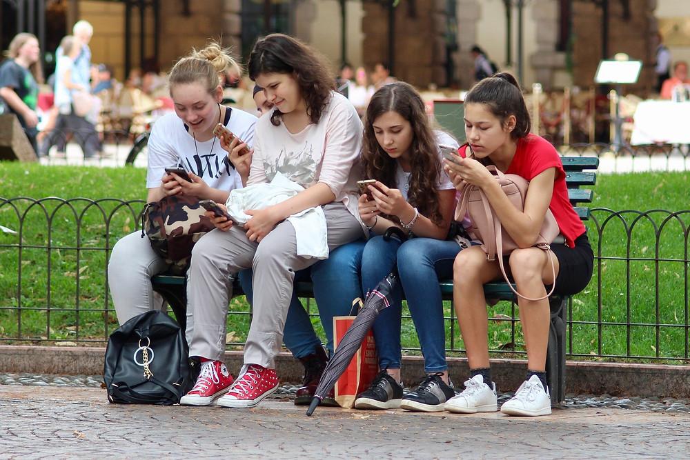 Teenage girls on their mobile phones